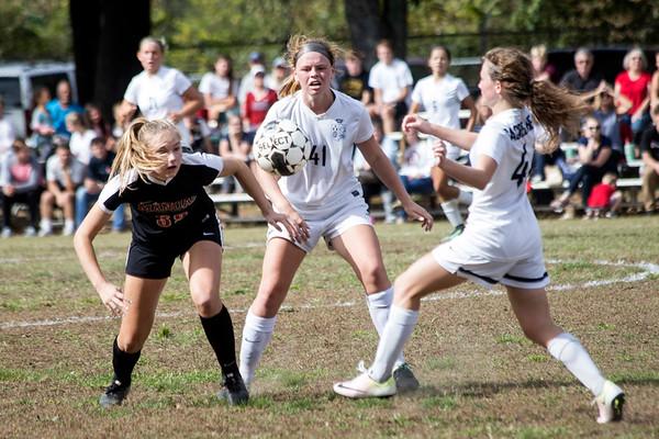 Manual's Savina Zamborini battles Sacred Heart's Meg Williams and Brielle Heuglin during the 7th Region Soccer Final. 10/21/17