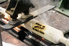 A Los Angeles Dodgers bat is put through a burn branding machine at the Louisville Slugger Factory on Monday as part of a batch being prepared for the World Series. 10/23/17