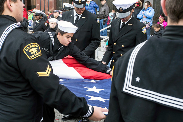 Members of the US Navy's Sea Cadets carefully fold the giant flag used in the Veterans Day Parade. 11/11/17