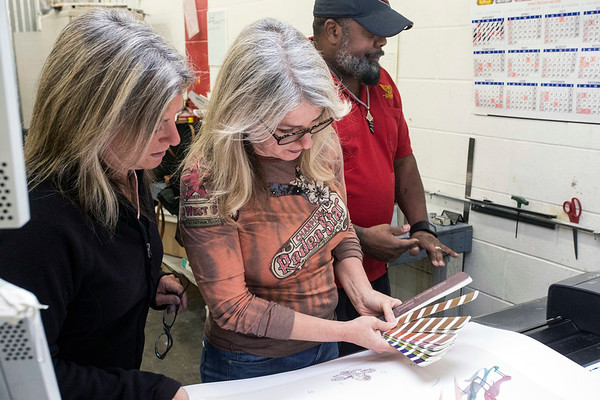 Sisters Jeaneen Barnhart and Doreen Barnhart-DeHart look at color schemes as they fine tune their design for the 2018 Kentucky Derby Festival poster on Thursday morning. 1/25/18