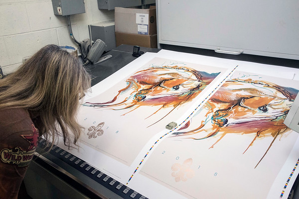 Doreen Barnhart-DeHart takes a closer look at two versions of her 2018 Kentucky Derby Festival poster design on Thursday at Clark and Riggs Printing. 1/25/18