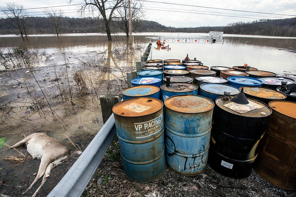 A dead deer floats near racing fuel barrels at the flooded entrance to the Ohio Valley Dragway on south Dixie Highway near West Point on Sunday afternoon. 2/25/18
