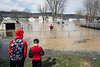 Children watch from dry land as West Point residents wade and row along the Elm Street properties flooded by the rising Ohio River. 2/25/18
