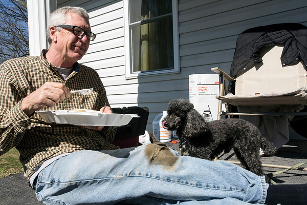 Joe Currell and his poodle Nick take a food break during flood clean-up on their Elm Street home in West Point, KY on Saturday. 3/3/18