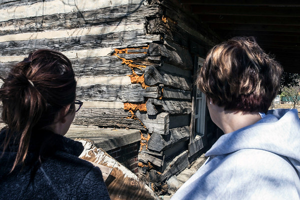 Elizabeth Nifong surveys the damage done to a corner wall on her family's 230-year-old cabin in Utica, Indiana on Sunday as the community recovers from recent floodwaters. 3/4/18