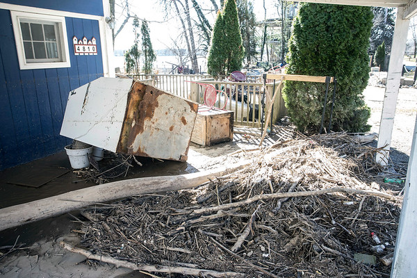 Mounds of driftwood and scattered debris wait to be cleaned at homes in Utica, Indiana after floodwaters ravaged the shore last week. 3/4/18