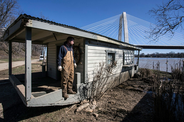 Chad Johnson surveys the damage to his property from the deck of a shanty that was lifted by rising floodwaters and moved several yards west of its normal concrete slab on Upper River Road in Utica, Indiana. 3/4/18