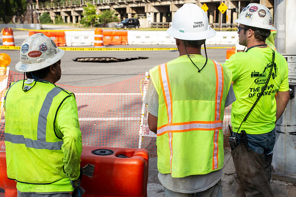 MSD crews consult with LG&E workers after a sinkhole appeared near the corner of Liberty Street and Baxter Avenue on Thursday afternoon. 8/3/18