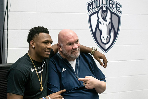 Moore High School defensive end JJ Weaver poses with head coach Rob Reader during a college commitment party on Friday. 11/30/18