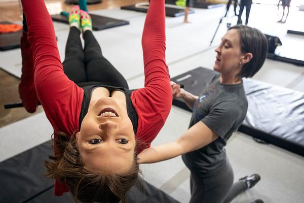 Suspend Louisville instructor Courtney Lantz guides Courier Journal reporter Maggie Menderski through a trapeze lesson. 2/2/19
