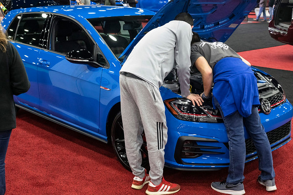 Spencer Hoskins and Jack Medley inspect the engine of a 2019 VW Golf GTI during the Louisville Auto Show on Saturday afternoon. 2/23/19