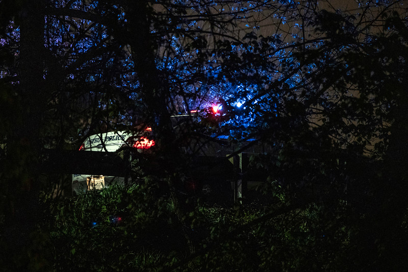 The flashing blue lights of an LMPD cruiser illuminated the trees around I-264 near Bells Lane on Thursday night after multiple people were injured in a shooting. 4/18/19