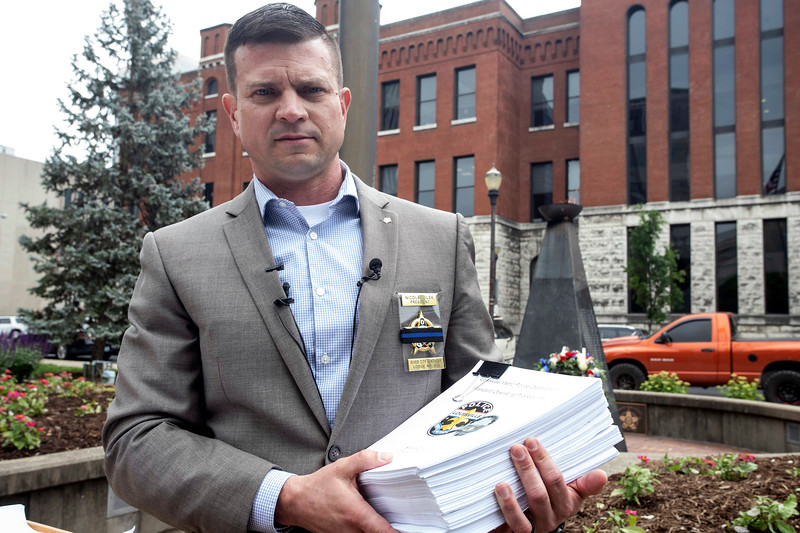 FOP President Nicolai Jilek held the recently expanded 822-page LMPD standard operating procedures during a press conference on Friday afternoon. 5/10/19