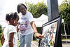 Ernestine Tyus looks at a framed photo collection during a memorial picnic in August for her grandson Ki'Anthony Tyus at Ballard Park. Ki'Anthony died as a passenger in a car crash during a police pursuit in December 2018. 8/17/19