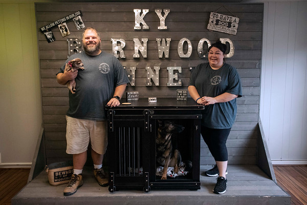 Roy and Toni Mills pose with their dogs Samantha and Diva alongside one of the custom built doghouses they produce at Kentucky Barnwood Kennels. 9/20/19