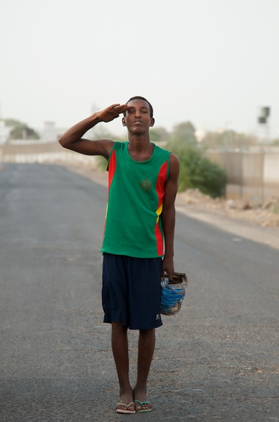 Day 314 -Like and share if you know the pothole guy.  The pothole guy stands watch outside the gate and with his trusty bucket and some dirt he's saving the roads of Djibouti one pothole at a time. And unlike most paid road construction workers, he always does it with a smile.  -JULY 16