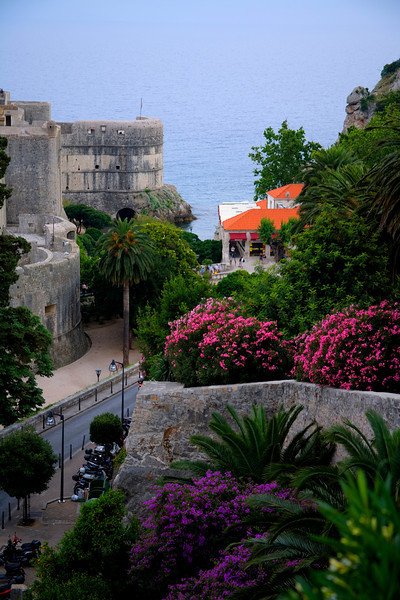 """Buy a Print""-The Walled City-Croatia-Dubrovnik has a long history of war, earthquakes, fires, and at one time rivaled Venice as a seaport. The walls run 2 km around the city and at some points are as thick as 6 meters. It was nice in the heat of the day to walk the dark and narrow passageways. Many of the homes were only accessible by climbing steep stairs. That grew old real quick as I searched for interesting doorways to photograph. This photo is the farthest point north of the city catching the edge of the wall, looking out to the Adriatic sea. This is a place you just want to meld into the history and spend time absorbing the city and beyond. Restaurants are everywhere and you just want to try everything. This a place you don't want to breeze through. Come and spend time. For those following ""Bachelorette"" on T.V., this is their next stop, next week!"