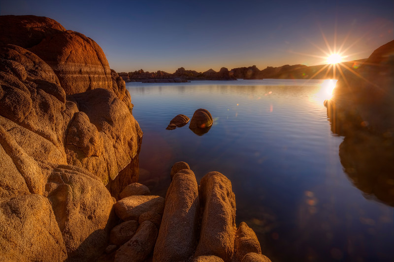 "Sunrise at Watson Lake, Prescott, Arizona<br /> One of my favorite spots to photograph in Arizona is the ""The Dells"", Prescott, Arizona. The boulders are flung around  everywhere making some interesting fun photography. This sunrise shot was one of my 1st, before I started climbing and jumping around different boulders looking for better and better vantage points. I remember taking a leap between a rather deep crevasse and slammed my brand new Canon 16-35mm into the granite wall. It bounced back and slammed me in the nose giving me quite a jolt. The lens managed to stay in one piece, though the sky light filter got bent up pretty good. Saved by a cheap filter. That's the way to do it!"