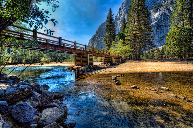 Walking Bridge in Yosemite Valley, California<br /> Surrounded by towering mountains, the Merced River meanders through Yosemite Valley. I could spend days here just wandering along the river banks, enjoying the cool breezes, wild life and grassy fields that make up the valley. This walking bridge made a good photographic spot along the trail. I had to wait for a family that was forever enjoying the water under the bridge. I remained patient and they finally moved on.