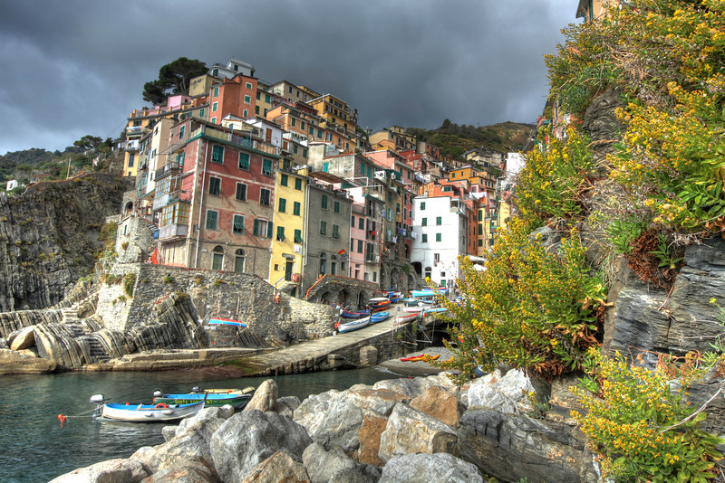 """Riomaggiore, Cinque Terre, Italy<br /> I thought I would take advantage of the wild flowers growing out of the cliffs in Riomaggiore, as the storm clouds grew above the town. It 's quite impressive how the """"cliff towns"""" of Cinque Terre"""" are carved out of the sides of the mountain that ends in the Ligurian Sea. All the homes and businesses are painted in different pastel colors. A very magical place that has enjoyed tourist for hundreds of years. For photographers and artist, it's a unique and special wonderland."""
