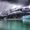 Margerie Glacier in Glacier Bay, Alaska-<br /> You feel like you're about as far away from civilization as you can get when you're here. The cruiseship gets about as close to the glacier as is safe and your eyes are completely focused on catching the sluffing off of ice called calving. We saw this huge arch-shaped piece of ice, more like something you would see at Arches National Park in Utah. We waited and then it came crashing down. I caught it all on video. Pretty exciting.<br /> <br /> This photo caught my attention because of the dramatic clouds that crawled up the side of the mountain heading towards the blue-hued glacier. The mammoth size of this flowing ice is quite awesome to see.