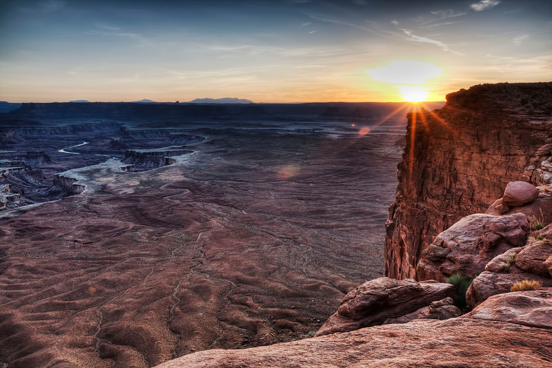 Sunset in Canyonlands, Utah<br /> I spent a number of nights and one early morning capturing this majestic location called, Green River Overlook in Canyonlands. This particular evening the wind was whipping up out of the canyon and I didn't dare let go of my tripod for fear it would end up in the deep crevasse that was just behind me. I stayed low to the ground for fear I would be thrown into the deep hole also.  A half  dozen of us  avid photographers were teetering on one rock all vying for our spot to catch the sunset. One by one they drifted away and I held my ground 'til the bitter end and the bitter cold.
