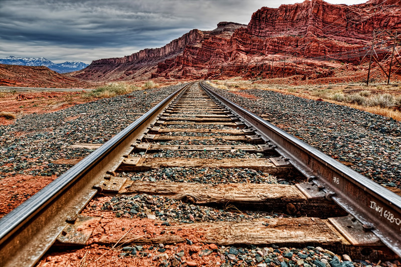 Moab, Utah-I Hear That Train a Comin'It's a funny feeling hanging around tracks as an adult. You're looking all around trying not to get caught. Don't know if it's legal or not to have your camera hugging a railroad tie, but it sure felt that way. To think as a child of 9 years old, chasing down a train and jumping on was something we did as kids for kicks. Let's just say I grew up in a roudy neighborhood near Pittsburgh where getting in trouble was par for the course.<br /> <br /> Left of these tracks (east) was Arches National Park and right (west) was Canyonlands National Park. Straight ahead was Moab. Spent 3 days there on a photography trip and enjoyed the heck out of it. Spring or fall is best times to go, unless you're into hitting the place after a snow storm. Summers are just too crowded with families on vacations.