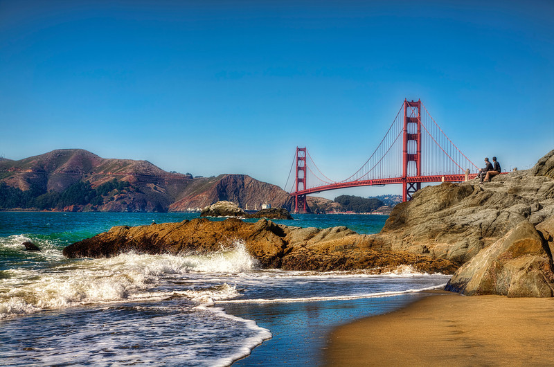 Golden Gate Bridge from Bakers Beach, San Francisco<br /> I was waiting patiently for the two guys sitting on the rocks to move on, but then I took another look and liked how they were seemingly fixated on the bridge. Beautiful summer day, weather was great, and tourist were crawling around the rocks trying to get a better view. Bakers Beach is in my opinion, is one of the better viewpoints for the Golden Gate Bridge.
