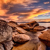 Rocky Coast of Lake Tahoe-The entire sky up behind us turned a blazing deep orange and yellows and lit up the rocks to eerie hues of tans and browns. The skies stayed pretty clear and blue for most of the 4 day trip to Lake Tahoe, Nevada this past week. Then one late afternoon thick clouds started rolling in, and I knew it was time to scope out the eastern shores of Lake Tahoe. We hiked down a steep cliff and searched for a spot to collect the granite rocks in the foreground of the scene, which is what I wanted the most. We found such a spot and claimed it before anyone could, probably a good hour and a half before sunset.<br /> <br /> Very few places I've been, match the incredible beauty of a deep alpine lake like, Lake Tahoe. Sandy beaches, waves, pine forest, comfortable temperatures, ski resorts, casinos, sailing, romantic cruises at sunset, hiking trails, waterfalls, rivers to go tubing and kayaking and much more. We stayed at a bed and breakfast in the pines the 1st night and then opted for a motel right on the beach. Off-season is a great time to go. Rates are cheaper and you don't fight the crowds.