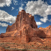 "The Majestic Arches, Utah<br /> Looking toward ""Wall Street"" to the west, I couldn't help but stop and take a shot of this huge red sandstone formation. When you're there, standing, looking up at these rocks, you're hypnotized by their shear size. The wind was literally blowing me over trying to get this shot. I had both hands on the tripod, waiting for a lull in the wind. When it came I had my shot. The clouds were moving so fast, I thought they might distort in the photo, especially taking 3 shots for an HDR. Arches National Park is an excellent hiking destination. Paths wonder everywhere and are pleasant and easy navigate. Try it!"