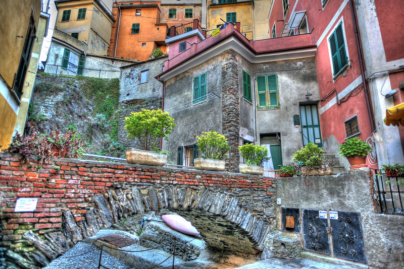 """""""Cliff Towns of Cinque Terre, Italy""""-Manarola is one of the 5 cliff towns that hover over the Ligurian Sea in northern Italy's Italian Riviera. This place is magical with it's pastel colored buildings hanging from the vertical hills. It's part of a National Park with hiking trails between each town. You can't really drive in these small towns, but a train seems to stop every 20 minutes to take you to the next town. We stayed in Levanto and commuted to each town to photograph and enjoy where ancient Romans use to vacation. East of the Cinque Terre, a town called Levanto is a great place to stay with everything Italy has to offer; great restaurants ,B&B's, beaches, shops, parks and tree-lines streets all tucked in a picturesque cove.  Check it out on Google Earth.<br /> <br /> This HDR shot was a walk half-way through town. Had to move trash cans and and as usual patiently wait for tourist to finish enjoying the spot before I could shoot. Part of the job. But what better place to just hang-out enjoying the moment."""