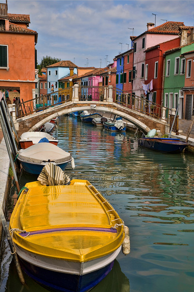 Yellow Boat in Burano, Italy<br /> Just a short boat ride from Venice is a small colorful island community of Burano. Famous for lace, it offers the traveler a rainbow of colors to enjoy, as each home is painted in individually, distinctive colors. Each time we visit Venice, we make plans to stop over in Burano for some serious photography. Venice is great, but quaint Burano has a personality all it's own. Walk the canal streets, relax at an outside restaurant, take in the locals, admire the rows of homes and gift shops across the island.. and don't forget your camera.