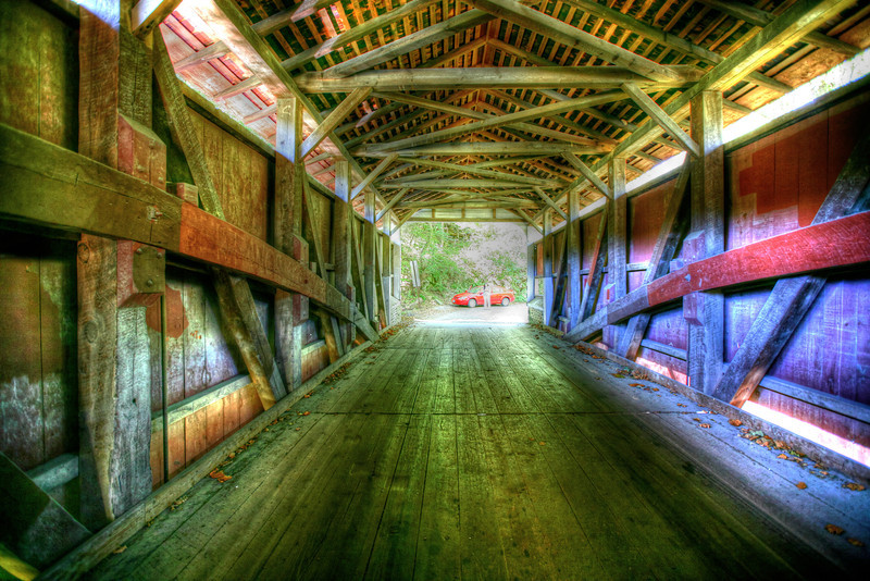 Covered Bridge, Oregon<br /> One summer we went to Oregon to do nothing but track down covered bridges and waterfalls. We traveled quite a bit around the state searching for the best. This one seemed cool, but can't remember the name of it. If you happen to know, drop a line. This one did pull out some color for an HDR shot. Looks like someone is waiting patiently at the other end of the bridge for me!