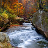 "Autumn at Wolf Creek, West Virginia-I flew out from Phoenix to spend a week exploring West Virgina in the autumn. New River Gorge was one of my planned destinations. Years ago we had stopped here and did a little hiking and I always wanted to come back. This time I was prepared, or so I thought I was. I had come with 3 camera format options:; large format, medium format and digital. I was never big into large format, because well it was big and heavy and hard to hike with. I did not bring a big enough tripod, so by mid day after hiking a mile to waterfalls, I lost patience and muscle and packed it away. It was expensive, $4.00 each time I took a picture. This photo of cascades on Wolf Creek, not far from underneath the New River Gorge in West Virgina, was one of my favorites of the trip. I used the digital camera this time. It was sunset, deep in a valley and was quite dangerous to take. This perspective took balancing my tripod on 3 rocks on top of a cliff, with nowhere to stand. I had no way to use the viewfinder, so I just kept shooting and adjusting until it worked. One of those ""don't try this at home"" moments.<br /> <br /> P.S: The airlines broke the large format camera into pieces on the way back to Phoenix. I put it on E-bay and sold it to some guy in Alaska who bought it for parts, for what I paid for it. Easy come, easy go!"