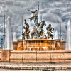 """Raices Fountain""-San Juan Puerto Rico-Walk along the Paseo de la Princesa of Old San Juan and enjoy the sight of the magnificent Raíces Fountain. Famous among lovers who sit and watch the sunset turn the fountain to golds and copper colors. Though I missed out on a colorful sunset, the clouds made up for it, making a great HDR image. Hardly a moment went by without someone sitting on the ledge and throwing a coin in the fountain. Do I hear a song coming on!!"