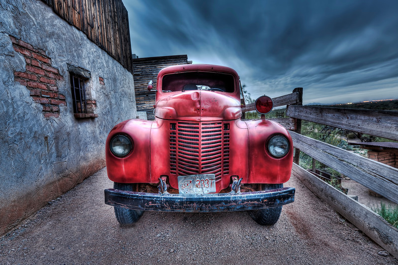 """The Old Red Fire Truck""-In Arizona at Goldfields Ghost Town sits this old fire truck peacefully at rest behind the rustic western stores. It was pretty far after dusk when I tried to pull the last light out of the sky to catch this HDR. Long exposures can create some fun effects. The colors can grow to be deeper. No color was added in post. I rarely enhance color in photoshop and this one was created by adding a small amount of contrast."