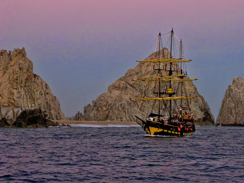 On the Tail of a Pirate Ship<br /> From the deck of the Cabo Escape in the open waters at the tip of Lands End in Cabo San Lucas, we spotted a rogue Pirate ship at sunset. The captain opened  in a full throttle to push the pirate ship into open waters. As we approached ever so cautiously, it turned out this was another one of those party ships with a bunch of drunk tourist. We turned quickly to the wind at starboard side and hulled butt out of there, as to not be dragged into the rum-soaked fumes of this out of control drunkard ship. At a safe distance we settle back to watch the sun sink into the distant ocean. As I awoke from my run away imagination I realized I was on the drunkard party boat.
