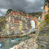 The Love Of Italy- Riomaggiore, Cinque Terre<br /> Riomaggiore is one of 5 Cinque Terre cliff towns located on the Ligurian Sea in Italy. I had spent the day scoping out possible evening shot locations and grabbed this one mid-day while a storm was brewing. I believe Cinque Terre is one of the most exciting places to come in Italy. It's got a lot to offer everyone. Easy train stops at each town, great restaurants, great hiking, water activities, you name it. I spoke to many Americans who come to this area and spend a week just hiking along the Ligurian cliffs between each of the villages. Great part they say is, anytime you want to stop, just go into the next village and catch the train that seems to run evey 20 minutes. We spent 3 days here and it definitely wasn't enough time.