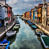 """Buy a Print""-Canals of Burano, Italy-A short distance by water taxi or water bus from Venice is a cute small island called Burano. Every home is painted a different color. Like Venice canals weave through the town from every direction with many bridge crossings. This island is definitely a tourist destination with shops and restaurants up and down the cobblestone walkways and corridors. As a photographer your camera never stops clicking as the ""photo ops"" simply unfold in front of you."