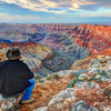 Taking in the Grand Canyon, Arizona<br /> Watching the colors of the canyon change as sunset approaches. The distant Colorado River falls into deep shadows, as it snakes through this mammoth hole it's created. Cameras are clicking all around me, as photographers try to catch this fleeting moment, as the sun sets. I'm probably in the way, sitting there just taking it all in, as if I'm the only one in the universe enjoying this incredible, into one of the 7 wonders of the world. And I really don't care that I may be in the way.. This moment is mine.