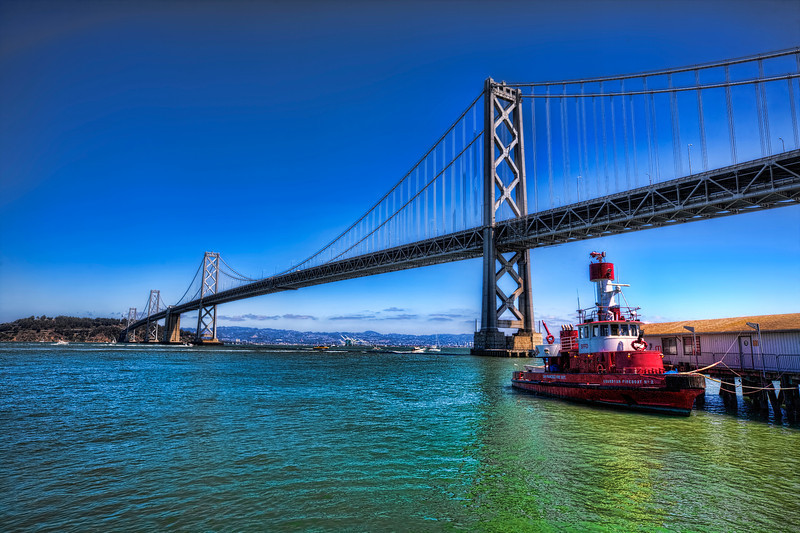 At Waters Edge, Oakland Bay Bridge, San Francisco<br /> A view of Oakland Bay Bridge from Embarcadero in downtown San Francisco. A foggy week was replaced with blue skies and warm temperature. The locals came out in groves as did tourist, as did photographers.