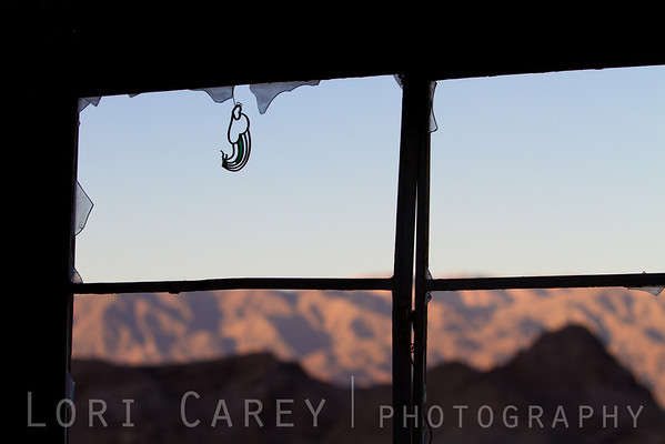 Suncatcher in window of abandoned cabin in the Mojave Desert