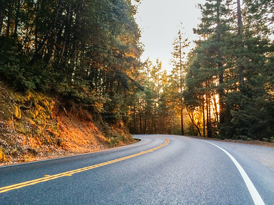 Empty, rural road with yellow dividing lines and sun setting behind trees