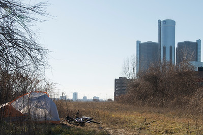 Homeless man's tent in foreground with bankrupt General Motors world HQ in background