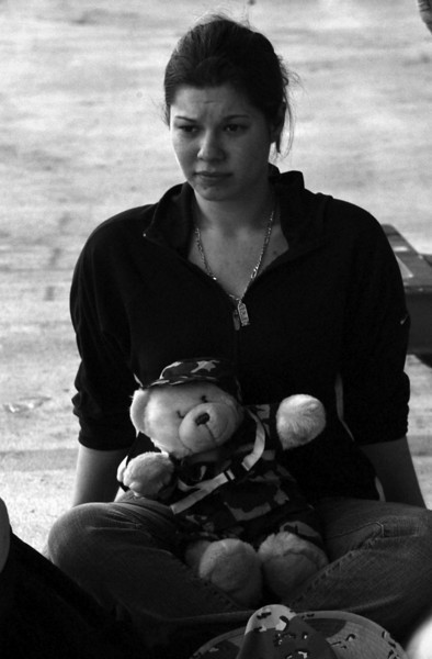 Alicia Ellis sits alone with a early christmas gift of a military teddy bear from her husband Petty Officer Ron Ellis of Longview, Wa. moments before he is to leave on a flight for Baharan for six month deployment, Saturday, November 27, 2004 at Marine Corp Base Hawaii in Kaneohe, Hawaii. Seventy-five sailors from Patrol Squadron Four (VP-4) left today to prepare for the arrival of a total of 360 sailors in support of Operations Iraqi and Enduring Freedom.   (AP Photo/Lucy Pemoni)<br /> <br /> Ê <br /> I