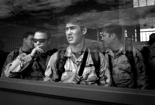 Some members of the 25th Infantry Division Light look out an airport window at the aircraft that will take them on a 24-hour plus flight to Afghanistan for a year or longer at Hickem Airforce Base in Honolulu, Hawaii, Tuesday, March 24, 2003.  About 5,000 soldiers from the 25th infantry in Hawaii are being sent to Afganistan and 4,000 to Iraq over the next two months . This will be the largest deployment from Hawaii for the 25th Infantry since the Vietnam War.  REUTERS/Lucy Pemoni