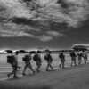 Soldiers from the 25th Infantry Light head toward the aircrafte and a 24-hour plus flight to Afghanistan at Hickem Airforce Base in Honolulu, Hawaii, Tuesday afternoon, March 24, 2003. In total,5,000 troops are being sent to Afganistan and 4,000 to Iraq over the next two months making this the largest deployment since the Vietnam War for the 25th infantry.  REUTERS/Lucy Pemoni