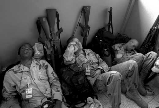 Members of the 25 Infintry Division Light sleeping after spending the night waiting for their 24-hour plus flight to Afganistan at Hickem Airforce Base in Honolulu, Hawaii, Tuesday, March 24, 2003.  About 5,000 soldiers from the 25th infantry in Hawaii are being sent to Afganistan and 4,000 to Iraq over the next two months  making it the largest deployment since the Vietnam War.  REUTERS/Lucy Pemoni