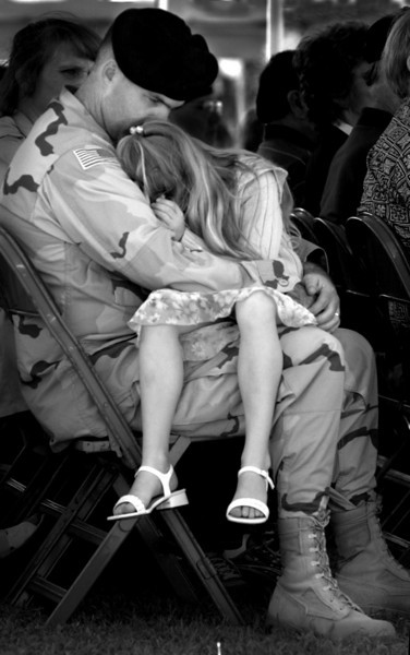 Major Randy Wardle, comforts his daughter Shyanne, 7, during the deployment ceremony at Sills Field at Schofield Barracks.  Maj. Wardle will be deployed to Afganistan next week for a full year.  Approximately 4, 500 soldiers from Hawaii will deploy to Afgananistan throughout March and April.  This is the largest deployment in history for the 25th Infantry Division. (AP Photo/Lucy Pemoni)