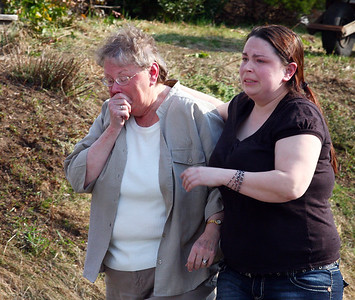 Catie Polizzotti comforts her mother Adele as they walk toward their School Street home in Groveland that was destroyed by fire Monday afternoon.